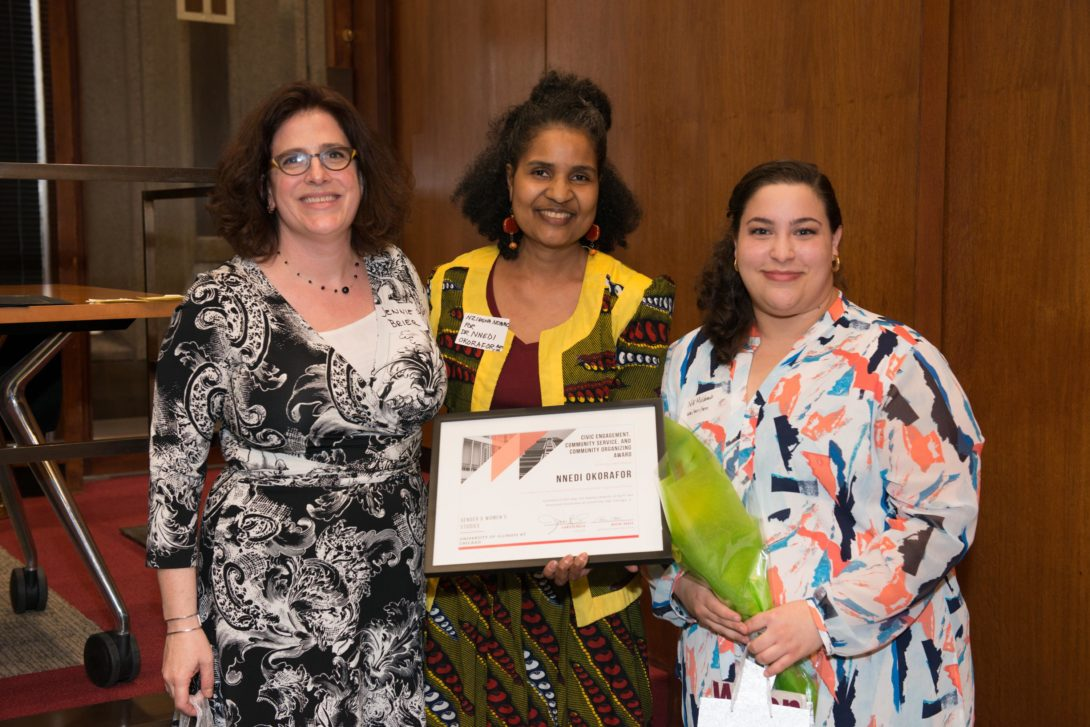 Jennifer Brier standing next to Nzingha Nommo, who is accepting an award for Nnedi Okorafor, and 2017 GWS graduate Niki Maldonado