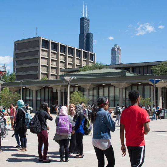 UIC students walk across the quad in groups.