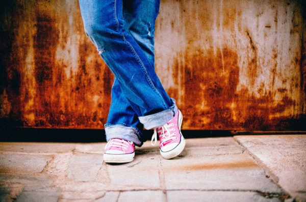 A person's legs crossed and pink converse on.
