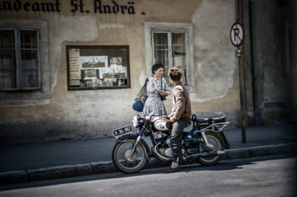 Old photo of a man sitting on a motorcycle and a woman standing next to him with them looking at each other.