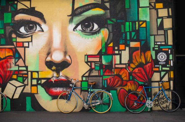 Mural of a woman's face with squares of color surrounding and a bicycle leaning against the mural wall.