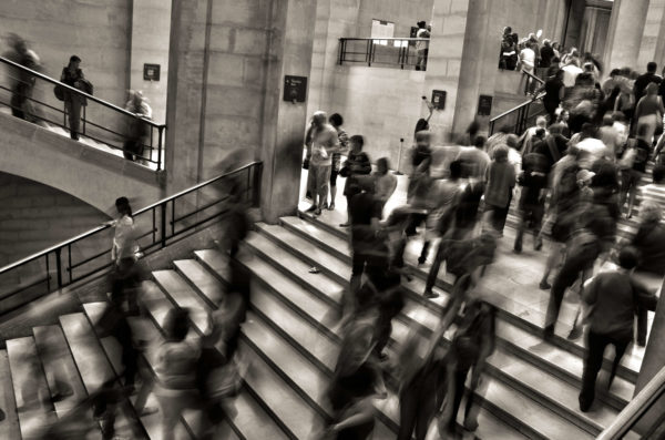 Blurred image of people walking up and down stairs at what appears to be a train station.