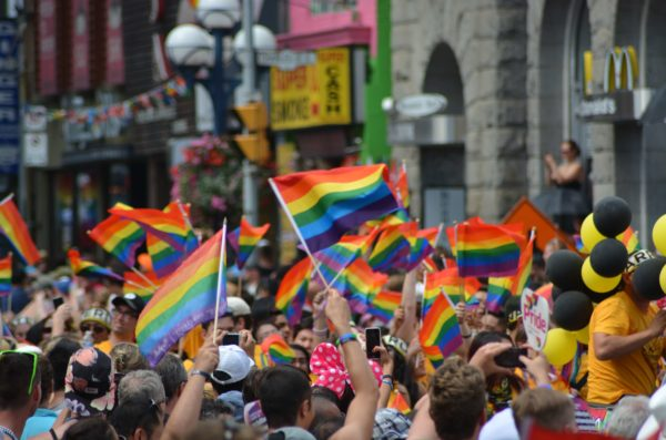 People holding rainbow pride flags at a rally or large public event.