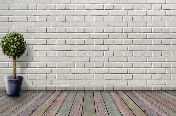 An open space with a white painted brick wall and a wood floor with faded colors painted on each floorboard.