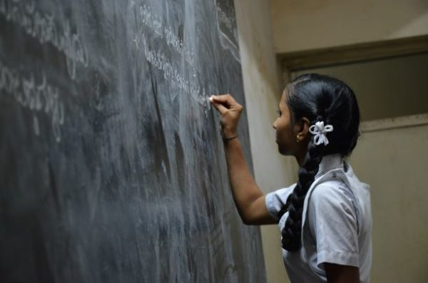 A young girl in a school uniform writing in chalk on a chalkboard.
