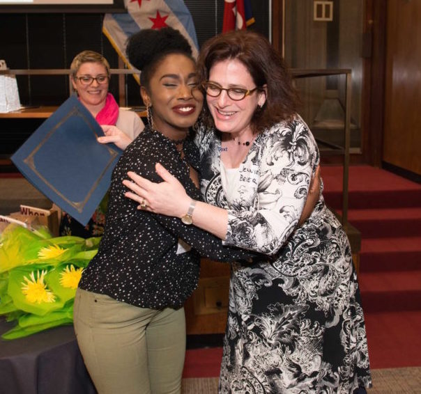 2017 GWS graduate Ariana Johnson is embraced by Professor Jennifer Brier during graduation ceremony.