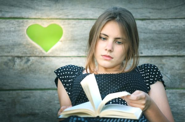 A woman reclining and looking at a book but not reading it, with a green heart in the background.