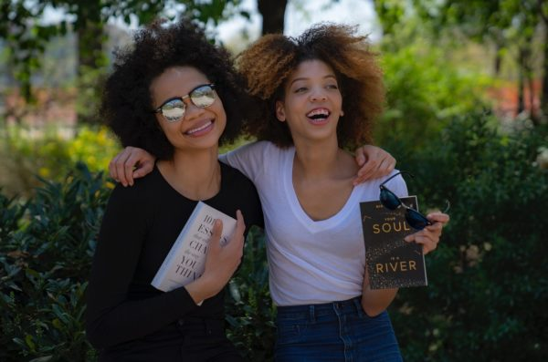 Two women holding books laughing together.