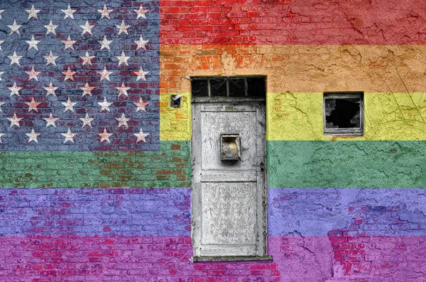 Wall painted with the American flag in rainbow colors with a door in the center of it.