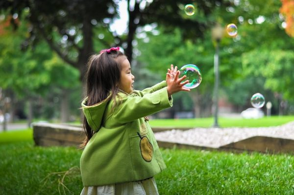 Asian child trying to catch a bubble.