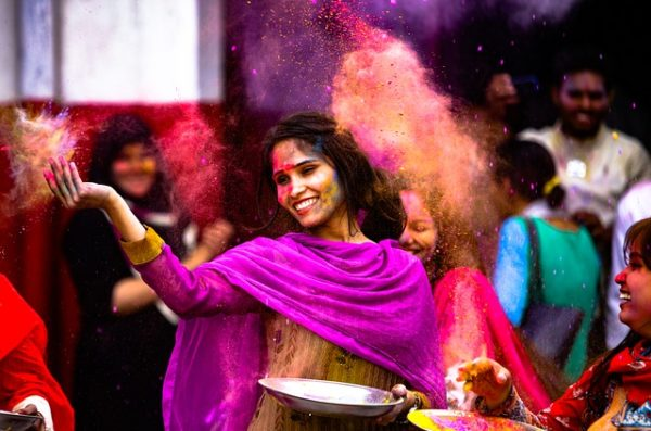Woman celebrating what appears to be an Indian wedding or similar ceremony, wearing a bright scarf and people are throwing brightly colored smoke in the background.