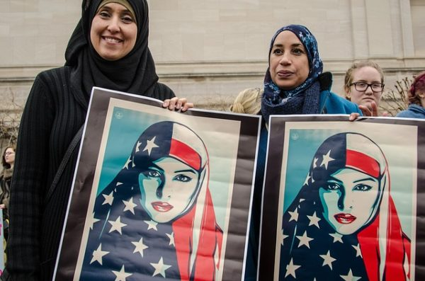 Muslim women holding paintings of muslim women clothed in American flag scarfs at what appears to be a protest.