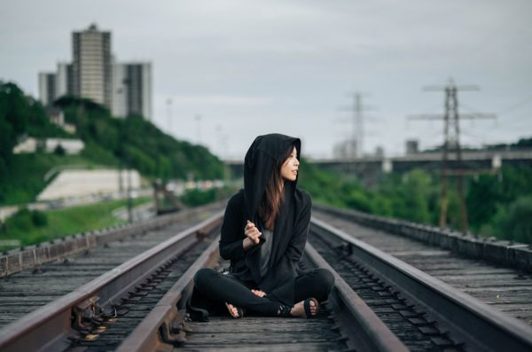 Woman in a hoodie sitting on train tracks.