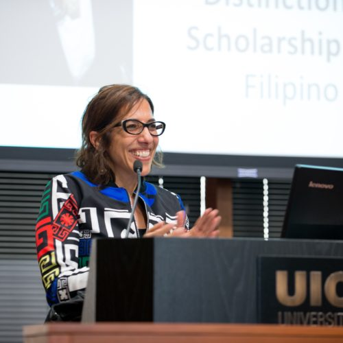 Professor Nadine Naber standing at a podium clapping.