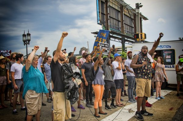 A group of people standing together at a protest with their hands and fists raised in the air.