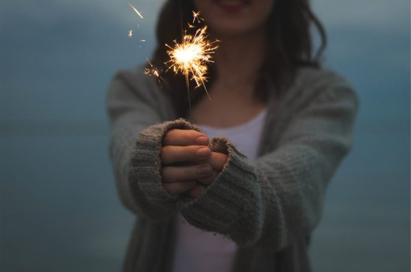 Woman holding a sparkler that is lit, in a foggy background.