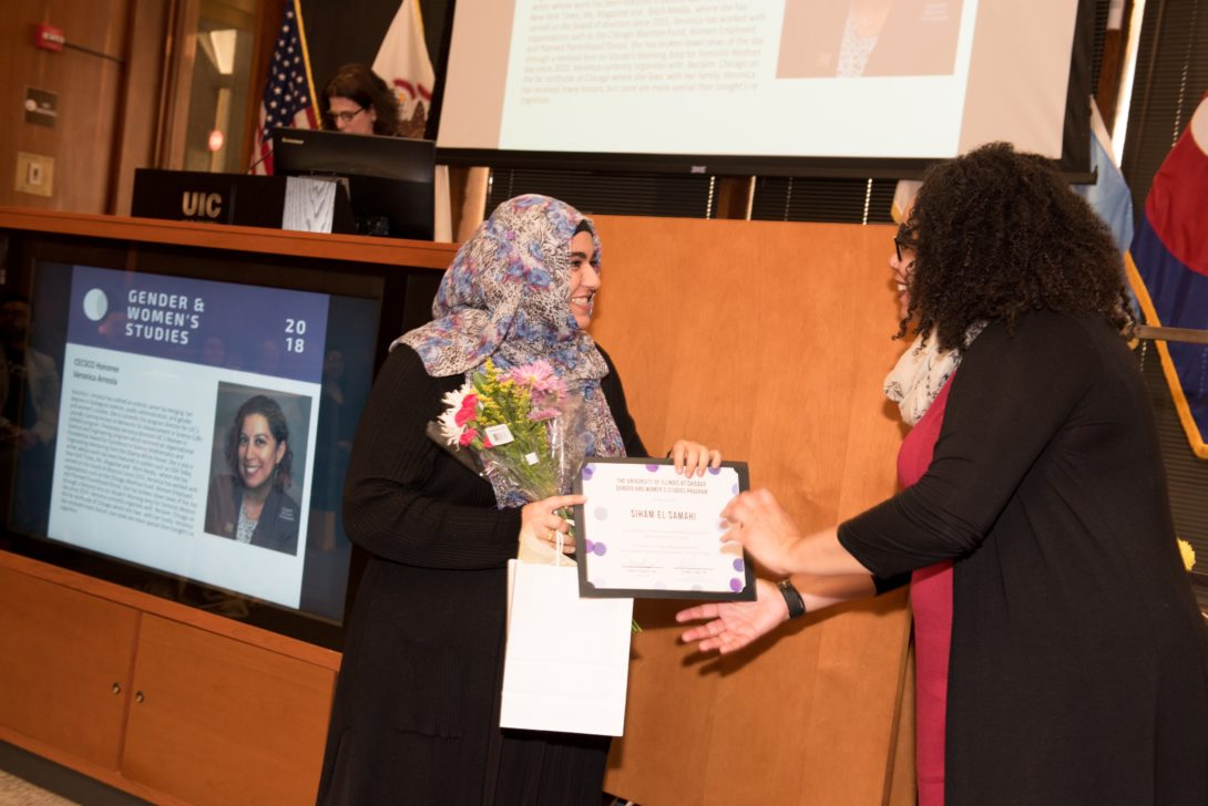 Two people stand in front of a podium. The person on the right hands the person on the left a certificate.