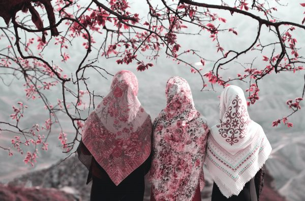 A group of people in hijabs stand beneath a tree.